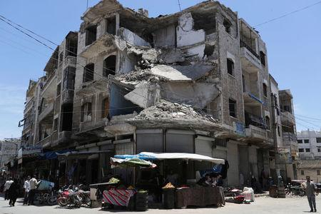 People walk past a damaged building in the city of Idlib