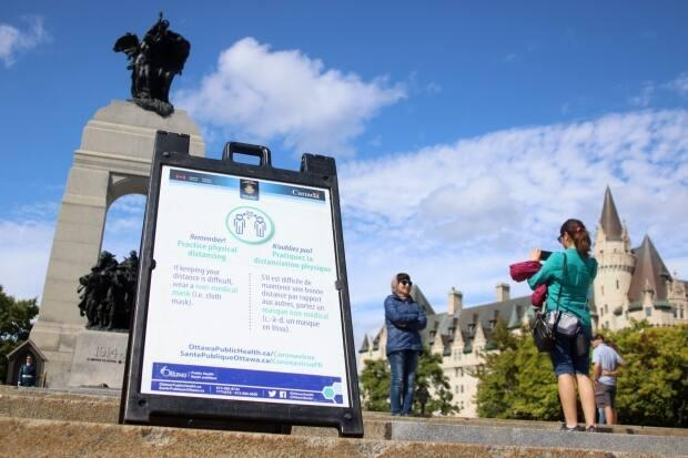 People take photos near the National War Memorial in Ottawa on Sept. 12, 2021, during the fourth wave of the COVID-19 pandemic. (Trevor Pritchard/CBC - image credit)