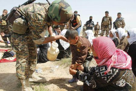 A member of the Kurdish Peshmerga forces helps people from the minority Yazidi sect who were newly released, on the outskirts of Kirkuk April 8, 2015. REUTERS/Ako Rasheed