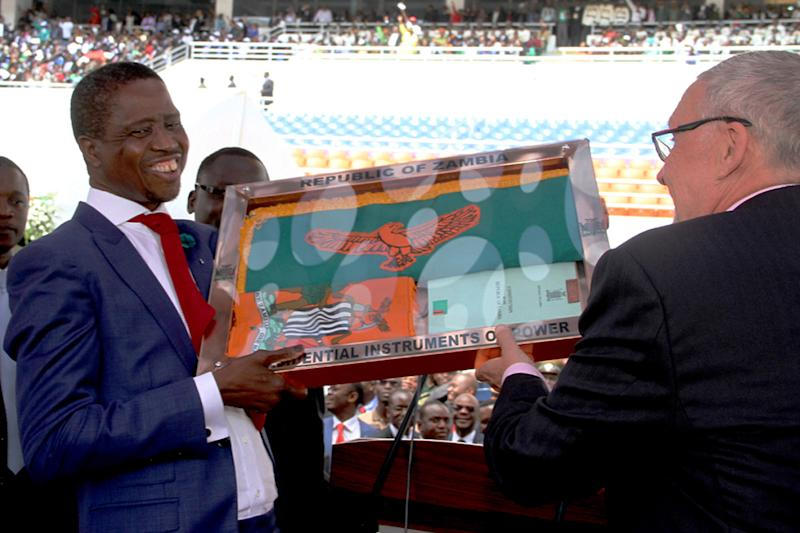 Zambia's newly elected President Edgar Lungu (L) receives the instruments of power from acting president Guy Scott (R) after being sworn in as Zambia's president, at the Heroes National Stadium in Lusaka on January 25, 2015 (AFP Photo/Salim Dawood)