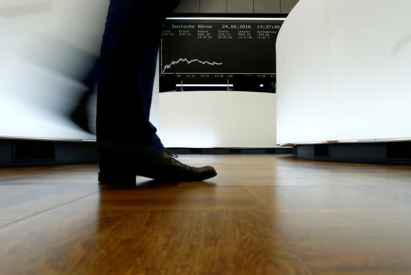 FILE PHOTO:  A trader walks past the German DAX Index board on the trading floor at the Frankfurt stock exchange
