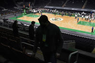 Boston Celtics employees leave their seats during the half time break in an NBA basketball game between the Boston Celtics and the Sacramento Kings, Friday, March 19, 2021, in Boston. TD Garden officials are preparing for the return of a limited amount of fans starting the week of March 22. (AP Photo/Elise Amendola)