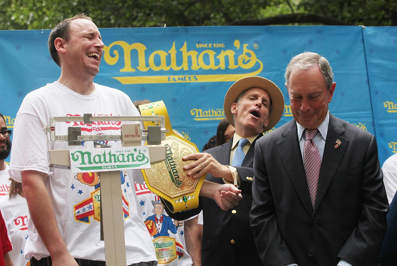 NEW YORK, NY - JULY 03: Men's world record holder Joey Chestnut (L) is weighed as New York City Mayor Michael Bloomber (R) looks on during the Nathan's Famous Fourth of July International Hot Dog Eating Contest weigh-in ceremony on July 3, 2013 in the Brooklyn borough of New York City. The annual hot dog eating event is expected to draw up to 40,000 fans on July 4, in the Coney Island section of Brooklyn. (Photo by Mario Tama/Getty Images)