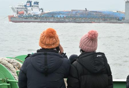 Family members of victims onboard the sunken ferry Sewol look on during its salvage operations at the sea off Jindo