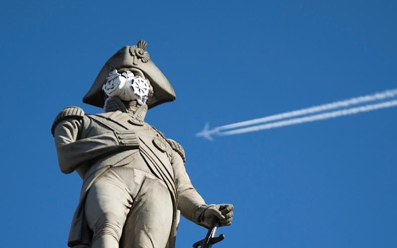A clean air mask is seen placed on the top of Nelson's Column by Greenpeace activists to protest against air pollution quality in London and cities across the UK - Matt Dunham/AP