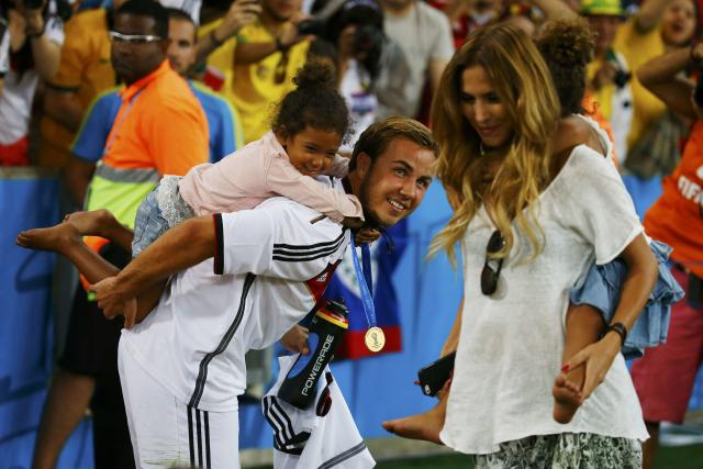 Germany's Mario Goetze and his girlfriend Kathrin Brommel (R) carry the twin daughters of teammate Jerome Boateng, Soley and Lamia, at the end of during their 2014 World Cup final against Argentina at the Maracana stadium in Rio de Janeiro July 13, 2014. REUTERS/Kai Pfaffenbach (BRAZIL - Tags: SOCCER SPORT WORLD CUP ENTERTAINMENT)