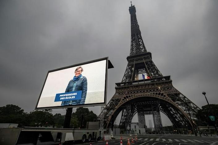 A portrait of a teacher who was mobilized during the pandemic is displayed on a giant screen in Paris on the eve of France's easing of lockdown measures (AFP Photo/Thomas SAMSON)