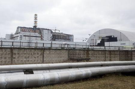 A general view shows a containment shelter for the damaged fourth reactor (L) and the New Safe Confinement (NSC) structure (R) at the Chernobyl Nuclear Power Plant, Ukraine, March 23, 2016. REUTERS/Gleb Garanich