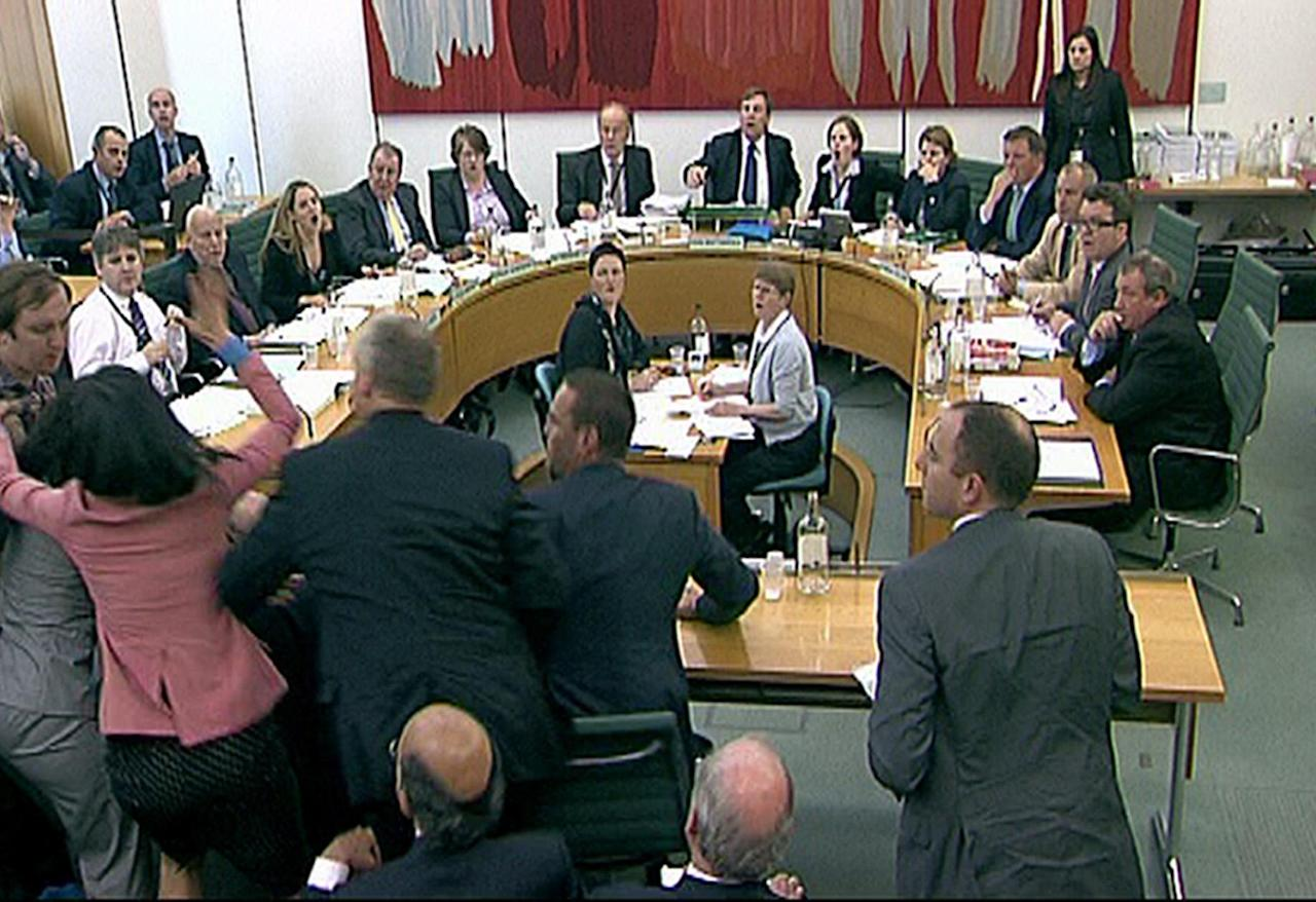 Committee members react after a protestor, left checked shirt , named on Twitter as Jonnie Marbles, tries to throw a paper plate covered in shaving foam over Rupert Murdoch as he gave evidence to a House of Commons Committee in London, Tuesday July 19, 2011, on the News of the World phone hacking scandal.(AP Photo/pa) UNITED KINGDOM OUT: NO SALES: NO ARCHIVE:
