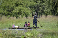 A mother holds her baby as she is transported by dugout canoe through floodwaters in the village of Wang Chot, Old Fangak county, Jonglei state, South Sudan Thursday, Nov. 26, 2020. Some 1 million people in the country have been displaced or isolated for months by the worst flooding in memory, with the intense rainy season a sign of climate change. (AP Photo/Maura Ajak)