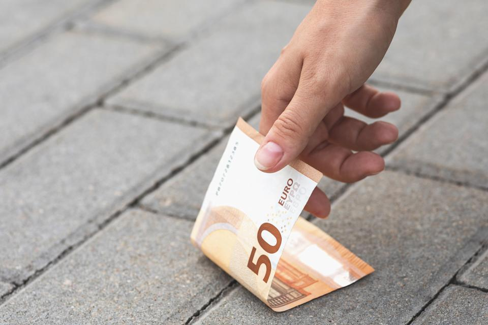 Lost and found money. Woman is picking fifty euro banknote from the ground.
