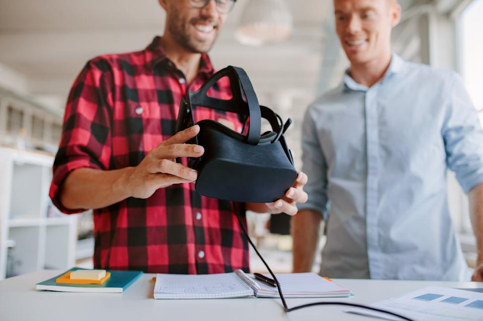 Shot of two men using virtual reality goggles in office. Business partners working in office, standing at a table with VR glasses.