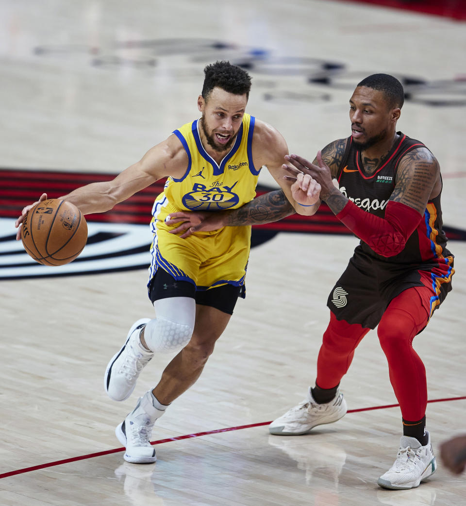 Golden State Warriors guard Stephen Curry, left, dribbles past Portland Trail Blazers guard Damian Lillard during the first half of an NBA basketball game in Portland, Ore., Wednesday, March 3, 2021. (AP Photo/Craig Mitchelldyer)