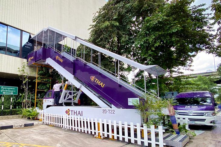Customers ascend the steps of a boarding ramp to enter the 'aircraft' (i.e. the restaurant).
