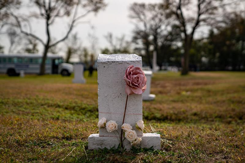Flowers are laid at a burial marker on Hart Island, a former prison and Nike missile silo site which is now the largest public burial ground in the United States, on October 25, 2019 in New York City. Family members of the deceased are allowed to visit their loved ones on one Saturday per month. Hart Island, located off the Northeast edge of the Bronx, is the largest public burial ground in the United States. Over one million people have been laid to rest at its 131 acre grounds. New York City's Department of Corrections utilizes sentenced inmates from Rikers Island to maintain the grounds of the island and to perform grave digging duties. The caskets are stacked three deep in a trench 36 inches below the surface, burying between 150 to 162 adults and 1,000 infant and fetal remains per trench which are marked with white headstones. Currently, a legislative package is making the rounds to transfer jurisdiction over Hart Island from the Department of Correction to the Department of Parks and Recreation. (Photo by David Dee Delgado/Getty Images)