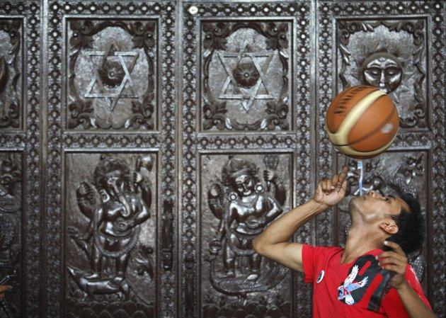 Thaneshwar Guragai spins a basketball on a toothbrush while holding the toothbrush in his mouth for exactly 22.41 seconds to break the last Guinness record of 13.5 seconds set by Thomas Connors of U.K, in Kathmandu April 19, 2012. REUTERS/Navesh Chitrakar