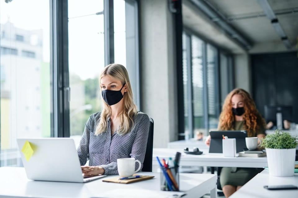 people with face masks back at work or school in office after lockdown