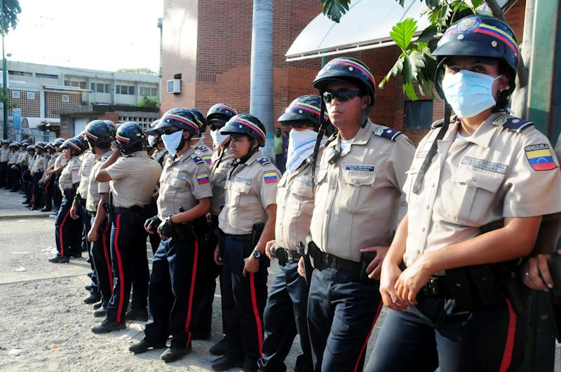 Venezuelan police officers stand guard outside the morgue where the bodies of prisoners killed in a riot were taken in Barquisimeto,Venezuela, Saturday, Jan. 26, 2013. A clash between National Guard soldiers and armed inmates led to a deadly riot Friday that reportedly left dozens of people dead. According to a local hospital director the death toll has risen to 61 and 120 injured. (AP Photo/Misael Castro/El Informador)