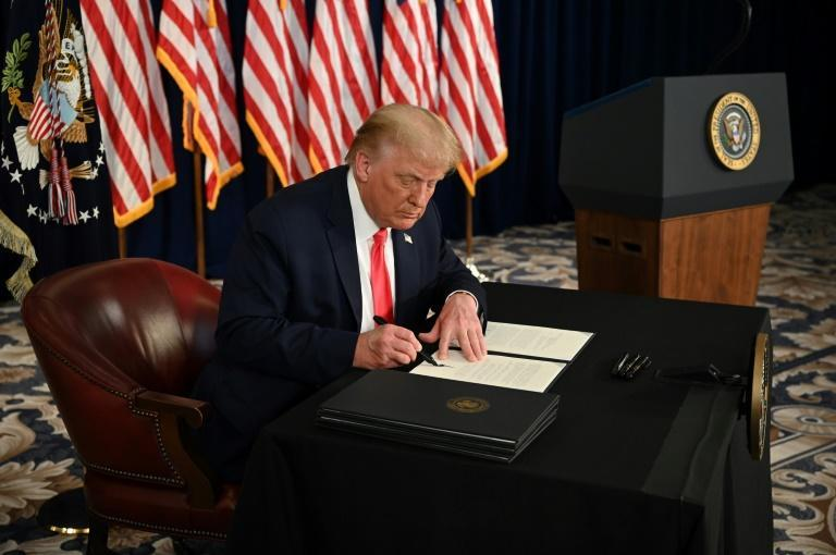 President Donald Trump signs executive actions extending coronavirus economic relief during a news conference at his golf club in Bedminster, New Jersey, on August 8, 2020