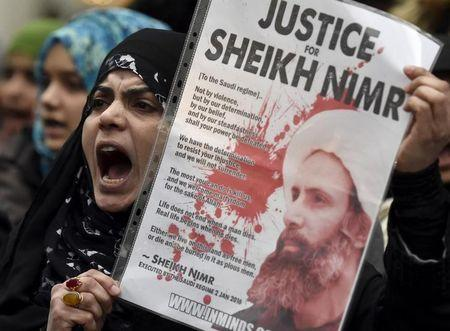 A protester holds a placard during a demonstration against the execution of Shi'ite cleric Sheikh Nimr al-Nimr in Saudi Arabia, outside the Saudi Arabian Embassy in London, Britain, January 3, 2016. REUTERS/Toby Melville