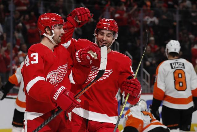 Detroit Red Wings left wing Darren Helm (43) is congratulated on his goal by teammate center Frans Nielsen (51) during the second period of an NHL hockey game against the Philadelphia Flyers, Sunday, Feb. 17, 2019, in Detroit. (AP Photo/Carlos Osorio)