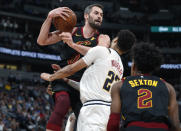 Cleveland Cavaliers forward Kevin Love, left, pulls in a rebound as Denver Nuggets guard Jamal Murray, center, defends while Cleveland guard Collin Sexton watches during the first half of an NBA basketball game Saturday, Jan. 11, 2020, in Denver. (AP Photo/David Zalubowski)