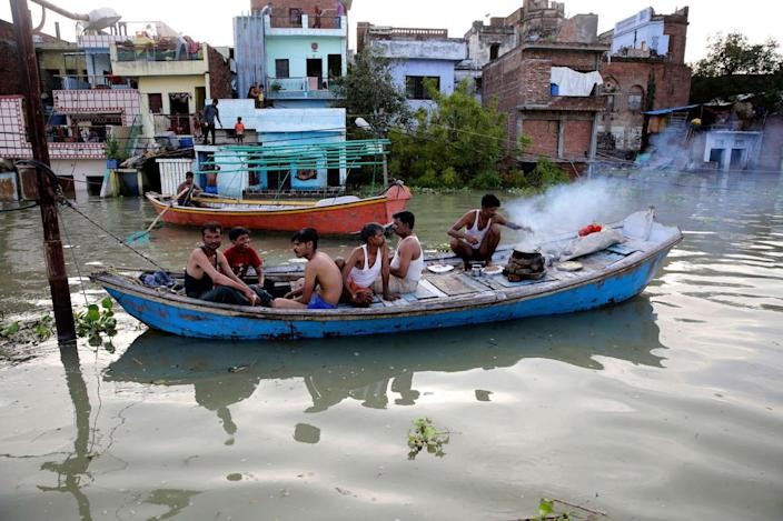 <p>Flood affected people cook food in a boat in front of submerged homes in Allahabad, India, Thursday, Aug. 25, 2016. (AP Photo/Rajesh Kumar Singh)</p>