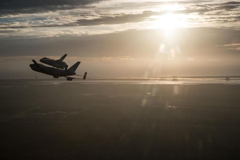 In this image provided by NASA the Space Shuttle Endeavour is ferried by NASA's Shuttle Carrier Aircraft (SCA) over the Kennedy Space Center in the early morning hours of Sept. 19, 2012 as it departs for California. Endeavour and the Shuttle Carrier Aircraft are in Houston after leaving Kennedy Space Center Wednesday. The ferry flight continues at dawn Thursday, heading to NASA Dryden, then on to Los Angeles Friday. This is the last flight for a space shuttle.  (AP Photo/Robert Markowitz, NASA)
