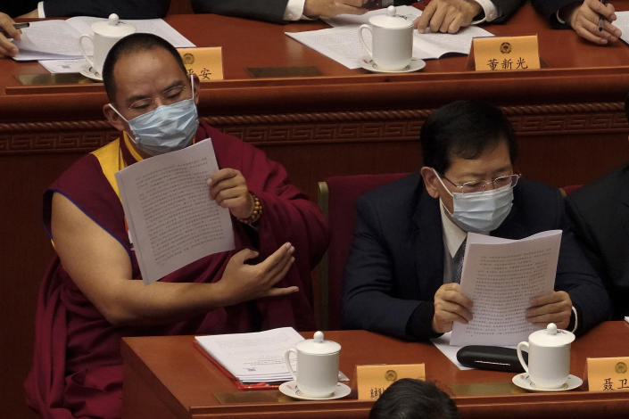 The 11th Panchen Lama Bainqen Erdini Qoigyijabu, left, a member of the National Committee of the Chinese People's Political Consultative Conference (CPPCC), left, wearing a face mask looks at a work reports during the opening session of the CPPCC at the Great Hall of the People in Beijing, Thursday, March 4, 2021. (AP Photo/Andy Wong)