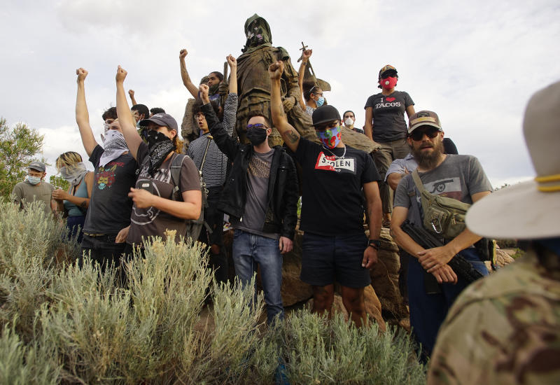 Demonstrators climb the statue of Don Juan de Oñate in Old Town Albuquerque. (Adolphe Pierre-Louis/ Albuquerque Journal via Zuma Wire)