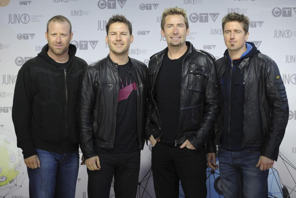"""FILE - In this April 1, 2012 file photo, members of Nickelback pose on the red carpet at the Juno Awards in Ottawa. Twitter has removed President Donald Trump's tweet of a Nickelback meme aimed at former Vice President Joe Biden because of a copyright complaint. The removed post, which featured the group's 2005 music video """"Photograph,"""" showed singer Chad Kroeger holding an edited photo of Biden, his son Hunter, a Ukrainian gas executive and another man. A Twitter spokesperson on Wednesday, Oct. 2, 2019,  said it responded """"to valid copyright complaints sent to us by a copyright owner or their authorized representatives."""" (AP Photo/The Canadian Press, Sean Kilpatrick)"""