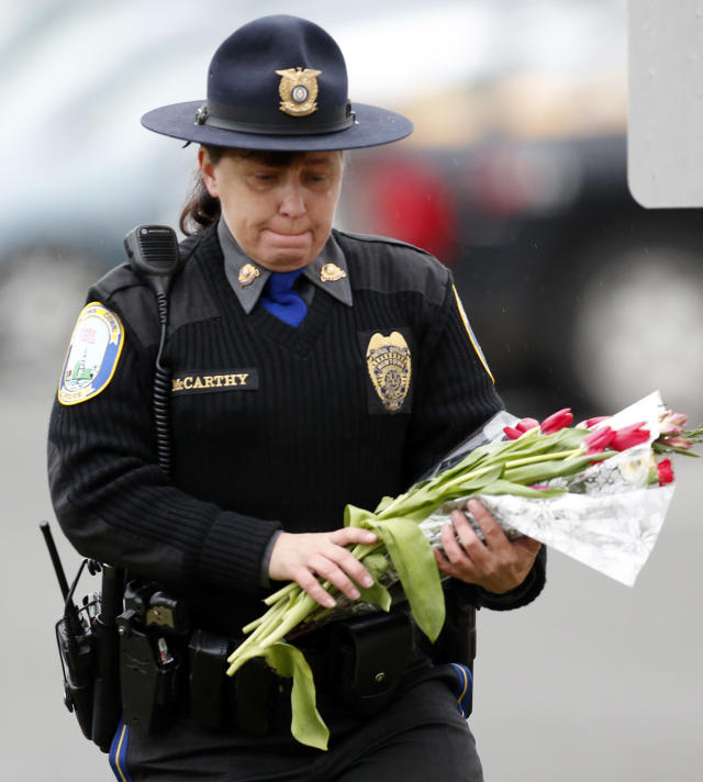 Newtown Police Officer Maryhelen McCarthy places flowers at a makeshift memorial outside St. Rose of Lima Roman Catholic Church, Sunday, Dec. 16, 2012, in Newtown, Conn. On Friday, a gunman allegedly killed his mother at their home and then opened fire inside the Sandy Hook Elementary School, killing 26 people, including 20 children. (AP Photo/Julio Cortez)