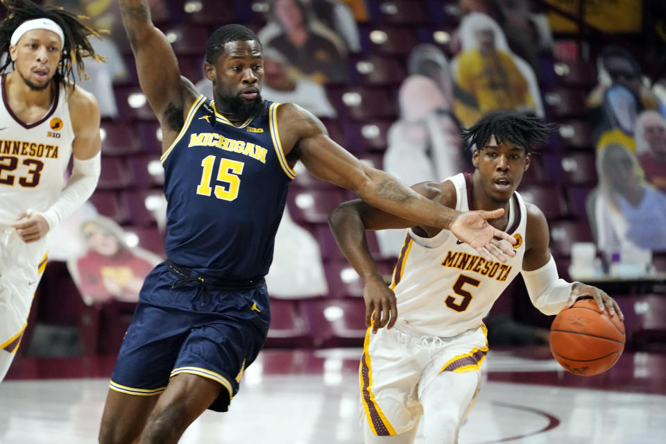 Michigan's Chaundee Brown (15) defends as Minnesota's Marcus Carr (5) drives the ball in the first half an NCAA college basketball game, Saturday, Jan. 16, 2021, in Minneapolis. (AP Photo/Jim Mone)