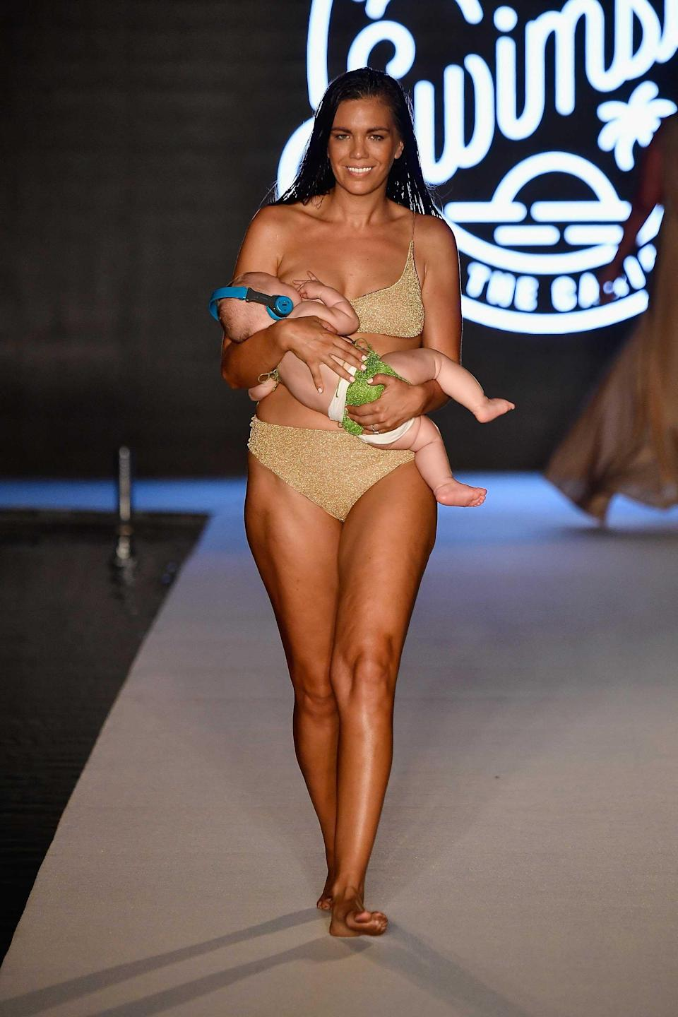 <p>Model Mara Martin walks the runway breastfeeding her baby for the 2018 <em>Sports Illustrated</em> swimsuit show during the Paraiso Fashion Fair in Miami at the W South Beach hotel on July 15. (Photo: Alexander Tamargo/Getty Images for Sports Illustrated) </p>