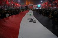 Pilgrims hold an Iraqi flag as they attend the ceremony of Shi'ite ritual of Arbaeen in Kerbala