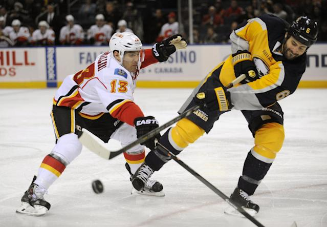 Calgary Flames center Mike Cammalleri (13), gives chase as Buffalo Sabres defenseman Mike Weber (6) slaps the puck away during the second period of an NHL hockey game in Buffalo, N.Y., Saturday Dec. 14, 2013. (AP Photo/Gary Wiepert)