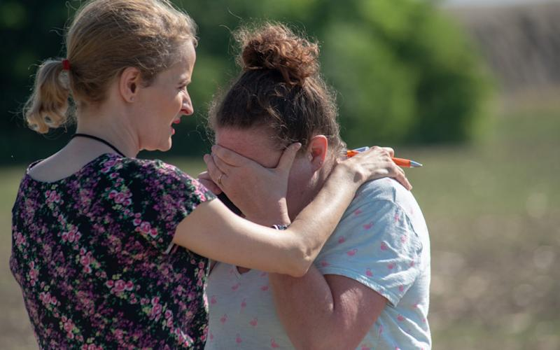 Substitute teacher Joanie Lynne, (L) consoles instructional assistant Paige Rose outside Noblesville West Middle School - Getty Images North America
