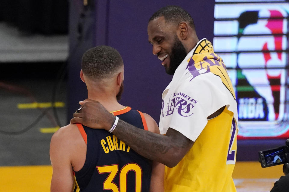 Los Angeles Lakers forward LeBron James, right, greets Golden State Warriors guard Stephen Curry after the Lakers defeated the Golden State Warriors 103-100 in an NBA basketball Western Conference Play-In game Wednesday, May 19, 2021, in Los Angeles. (AP Photo/Mark J. Terrill)