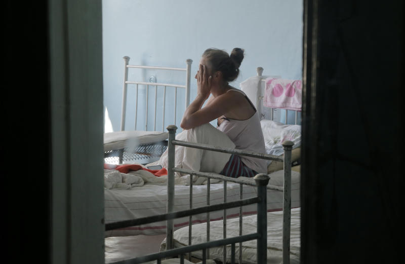 In this photo taken on Tuesday, Aug. 13, 2013, Yulia Yukhimets, 20, sits on her hospital bed in a hospital in the town of Ruzhyn, Ukraine. Yukhimets, together with nearly 60 guests, including 14 children, was delivered in an ambulance from a nearby village last week, suffering from food poisoning at her wedding celebrations. (AP Photo/Efrem Lukatsky)