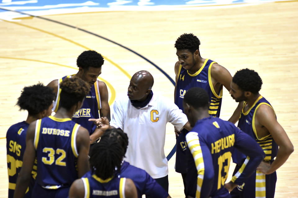 Bryan Spencer, center, head coach of Carver College talks with his players during the second half of an NCAA college basketball game against Florida International Monday, Dec. 21, 2020, in Miami. (AP Photo/Gaston De Cardenas)
