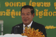 "Cambodian Prime Minister Hun Sen smiles as his delivers a speech during a handover ceremony at Phnom Penh International Airport, in Phnom Penh, Cambodia, Sunday, Feb. 7, 2021. Cambodia on Sunday received its first shipment of COVID-19 vaccine, a donation of 600,000 doses from China, the country's biggest ally. Beijing has been making such donations to several Southeast Asian and African nations in what has been dubbed ""vaccine diplomacy,"" aimed especially at poorer countries like Cambodia. (AP Photo/Heng Sinith)"