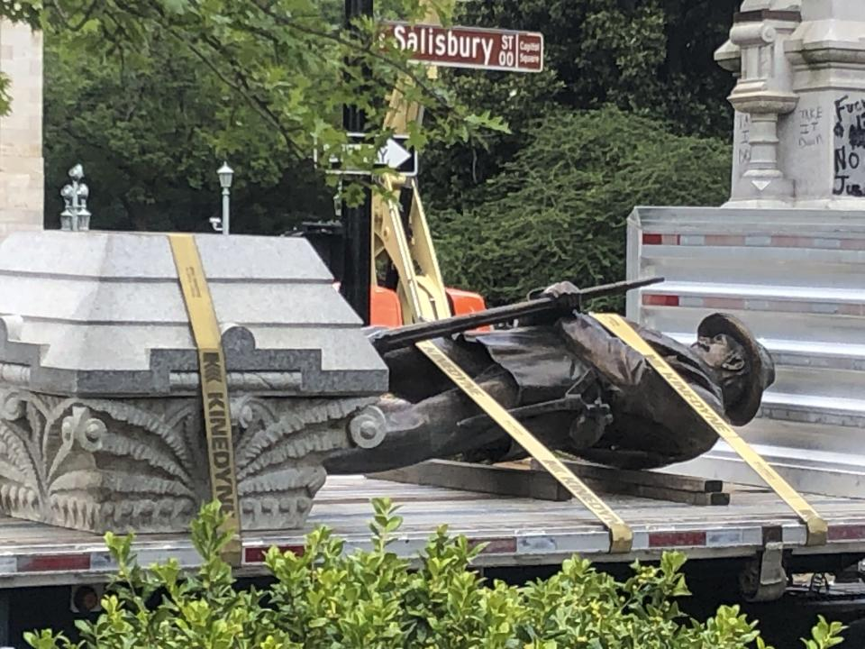 The statue of a Confederate soldier and plinth sit on a flatbed truck at the Old Capitol in Raleigh, N.C., on Sunday, June 21, 2020. After protesters pulled down two smaller statues on the same monument Friday, North Carolina Gov. Roy Cooper ordered the removal of several other monuments to the Confederacy, citing public safety concerns. (AP Photo/Allen G. Breed)