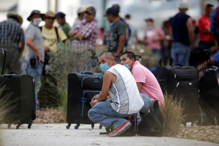 Migrants seeking for a U.S. work visa are seen waiting in a park of downtown of Monterrey