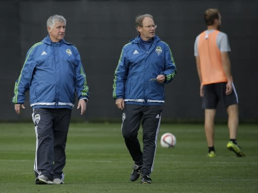 FILE - In this Oct. 27, 2015, file photo, Seattle Sounders head coach Sigi Schmid, left, watches player drills with assistant coach Brian Schmetzer, center, during an MLS soccer training session in Tukwila, Wash. Nearly two years after he died, Schmids presence and influence is being heavily felt heading into Saturdays MLS Cup final between Columbus and Seattle. (AP Photo/Ted S. Warren, File)
