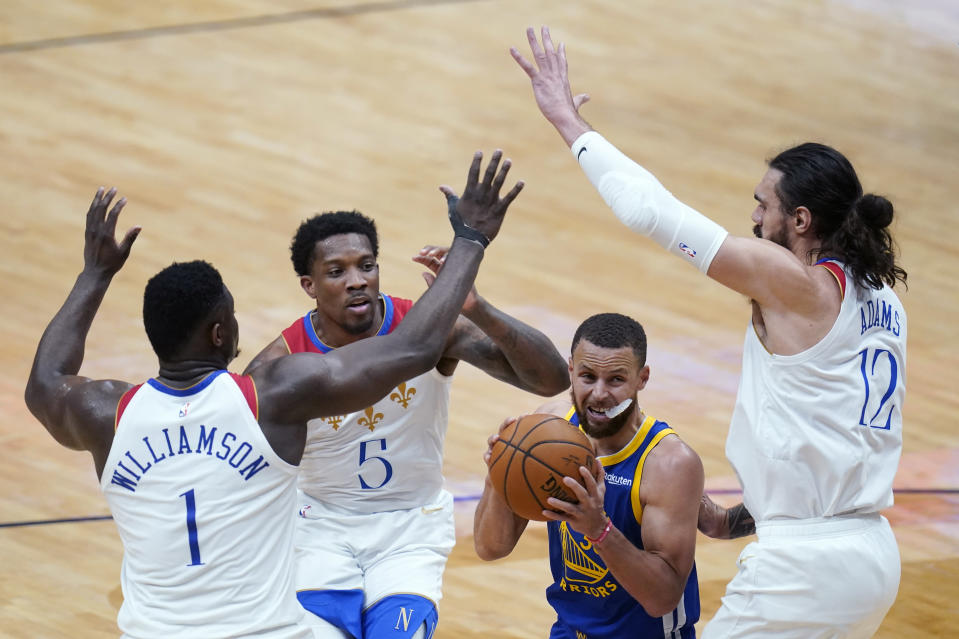 Golden State Warriors guard Stephen Curry throes to go to the basket under pressure from New Orleans Pelicans center Steven Adams (12), forward Zion Williamson (1) and guard Eric Bledsoe (5) in the first half of an NBA basketball game in New Orleans, Tuesday, May 4, 2021. (AP Photo/Gerald Herbert)