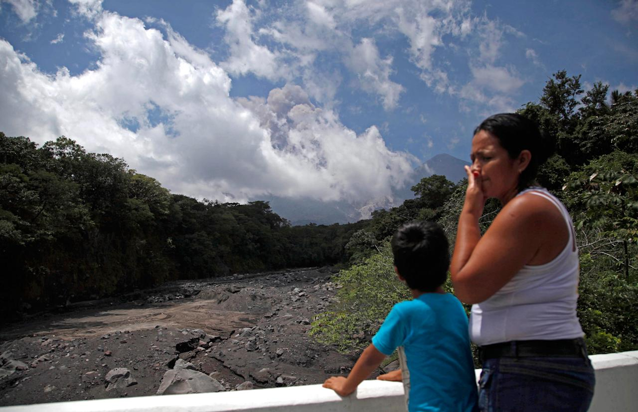 A boy watch plumes of smoke and volcanic ash rise from the Volcan de Fuego or Volcano of Fire, as seen from Palin, south of Guatemala City, Thursday, Sept. 13, 2012. The long-simmering volcano exploded into a series of powerful eruptions Thursday, hurling thick clouds of ash nearly two miles (three kilometers) high, spewing rivers of lava down its flanks and forcing the evacuation of more than 33,000 people from surrounding communities. (AP Photo/Moises Castillo)