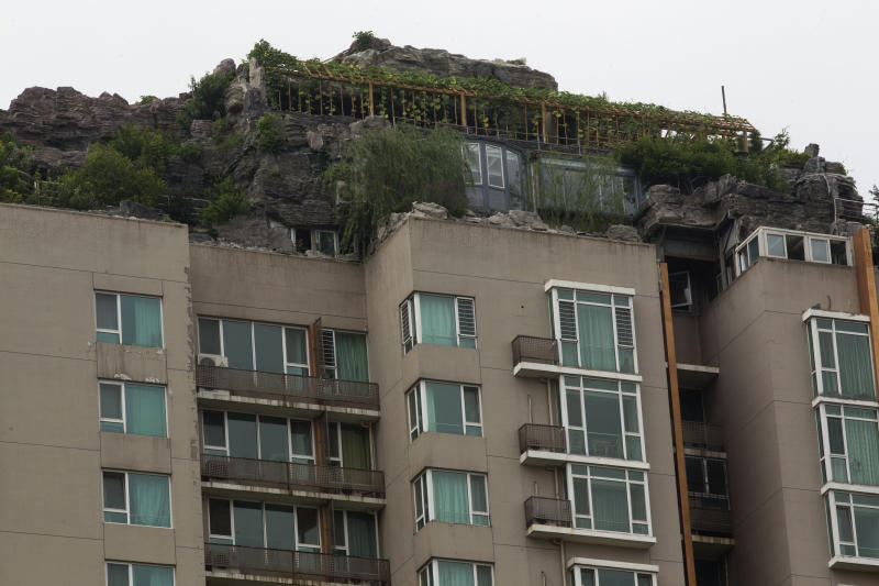 A rooftop villa complete with rocks and flora built on top of a high rise residential building stands in Beijing, China, Tuesday, Aug. 13, 2013. Beijing authorities are planning to demolish the bizarre rooftop villa embedded in rocks, trees and bushes that allegedly was built illegally atop a 26-story apartment block in the capital.(AP Photo/Ng Han Guan)