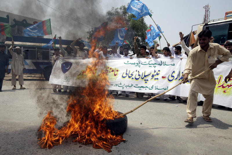 """Pakistani students of Jamaat-i-Islami burn tire and rally to condemn the resumption of NATO supplies to neighboring Afghanistan through Pakistan, in Peshawar, Pakistan, Thursday, July 5, 2012. The first truck carrying supplies to American and NATO troops in Afghanistan has crossed the Pakistani border after a seven-month long closure of the supply routes by Pakistan ended earlier this week. The banner reads, """"NATO supply is unacceptable."""" (AP Photo/Mohammad Sajjad)"""