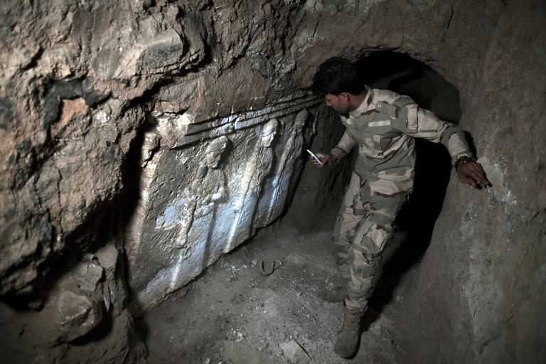 A member of the Iraqi troops stands next to archeological findings inside an underground tunnel in east Mosul, northern Iraq on March 6, 2017