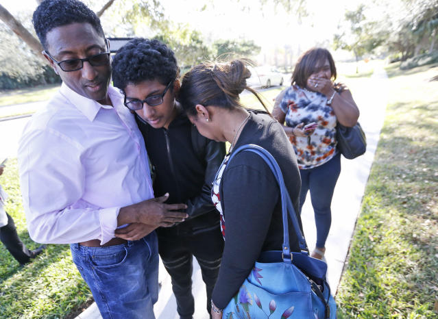 <p>Family members embrace after a student walked out from Marjory Stoneman Douglas High School, Wednesday, Feb. 14, 2018, in Parkland, Fla. The shooting at the South Florida high school sent students rushing into the streets as SWAT team members swarmed in and locked down the building. Police were warning that the shooter was still at large even as ambulances converged on the scene and emergency workers appeared to be treating those possibly wounded. (Photo: Wilfredo Lee/AP) </p>
